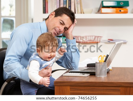 Stressed Man With Baby Working From Home Using Laptop - stock photo
