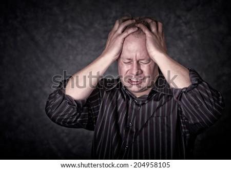 Stressed man with hands through hair on a gray background - stock photo