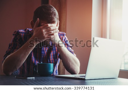 Stressed man with head in hands near laptop - stock photo