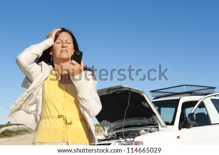 Stressed mature woman breakdown with car on remote road calling for assistance, for help on mobile phone, isolated with blue sky as background and copy space. - stock photo