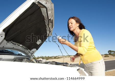Stressed mature woman breakdown with car on remote road checking oil and waiting for assistance, for help, isolated with blue sky as background and copy space.