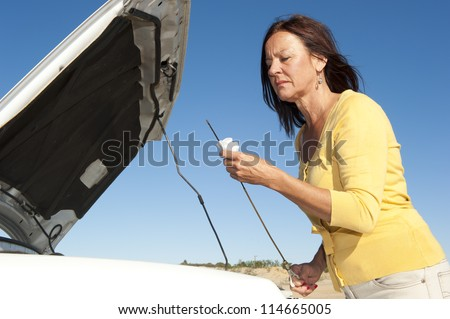 Stressed mature woman breakdown with car on remote road checking oil and waiting for assistance, for help, isolated with blue sky as background and copy space. - stock photo