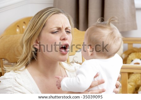 Stressed Mother Holding Baby In Nursery - stock photo