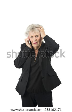 Stressed old woman talking on her mobile phone against a white background