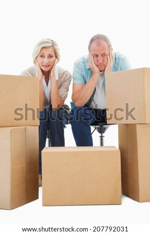 Stressed older couple with moving boxes on white background - stock photo