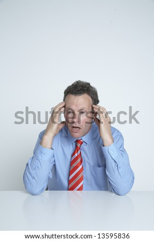 Stressed out businessman at his desk - stock photo