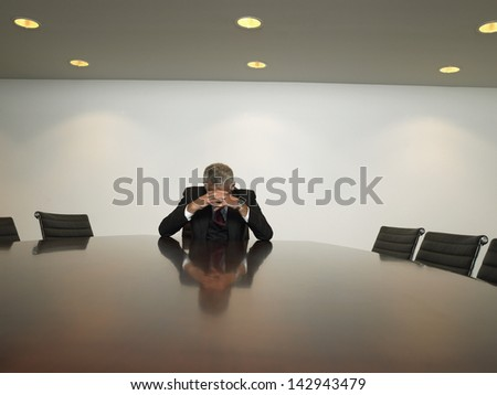Stressed out businessman with hands clasped sitting at table in conference room - stock photo