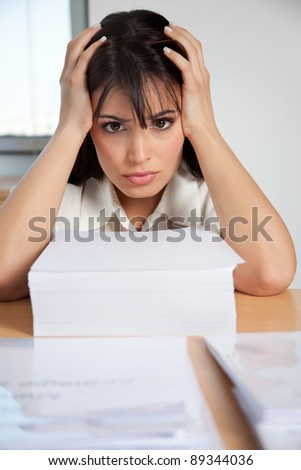 Stressed out businesswoman with pile of business papers at her desk - stock photo