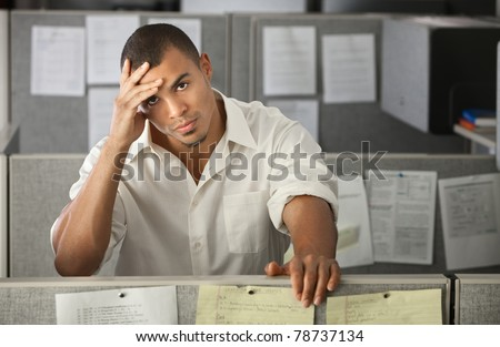 Stressed-out Latino office worker with hand on his head - stock photo