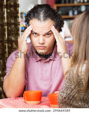 Stressed out man rubbing his head at table with friend - stock photo