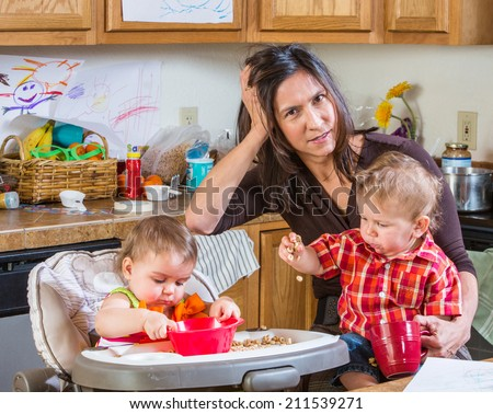 Stressed out mother in kitchen with her babies - stock photo