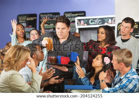 Stressed out restaurant waiter with group of angry customers - stock photo