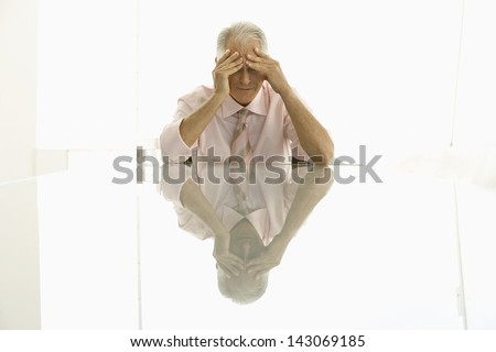 Stressed out senior businessman with hands on head sitting at conference table - stock photo