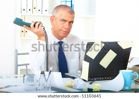 Stressed overworked mature businessman sitting at desk with phone and laptop with many note stickers - stock photo