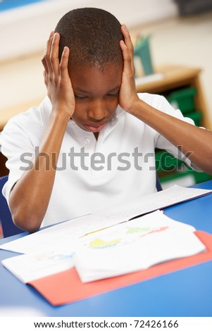 Stressed Schoolboy Studying In Classroom