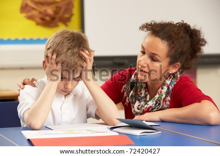 Stressed Schoolboy Studying In Classroom With Teacher - stock photo