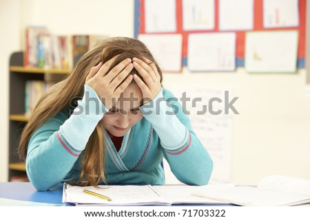 Stressed Schoolgirl Studying In Classroom - stock photo
