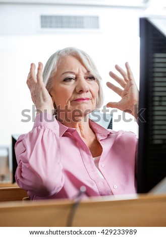 Stressed Senior Woman Looking At Computer In Classroom - stock photo