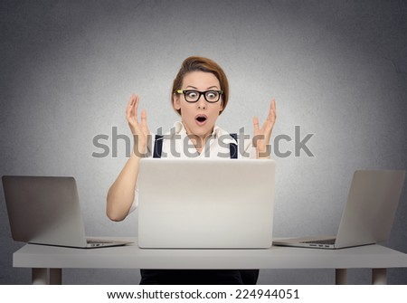Stressed shocked businesswoman sitting at table in front of multiple
