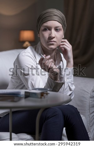 Stressed sick young woman smoking cigarette - stock photo