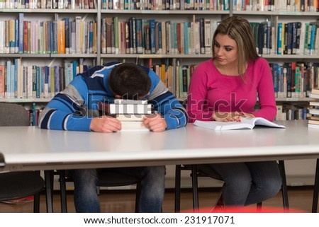Stressed Students Of High School Sitting At The Library Desk - Shallow Depth Of Field - stock photo