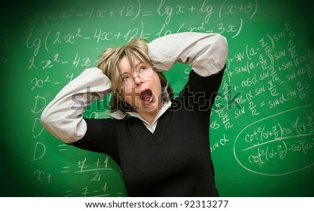 Stressed teacher against the background of a green chalkboard - stock photo