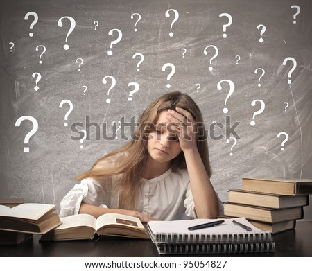 Stressed teenage girl doing her homework - stock photo