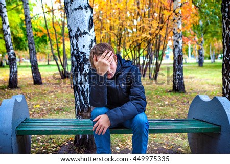 Stressed Teenager sit on the Bench in the Autumn Park - stock photo