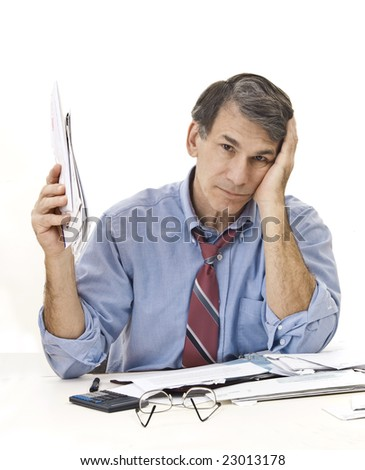 Stressed, tired, overworked businessman doing paperwork, worrying about the economy, his credit, etc. - stock photo