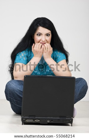 Stressed woman  looking scared and biting her nails in front of laptop - stock photo