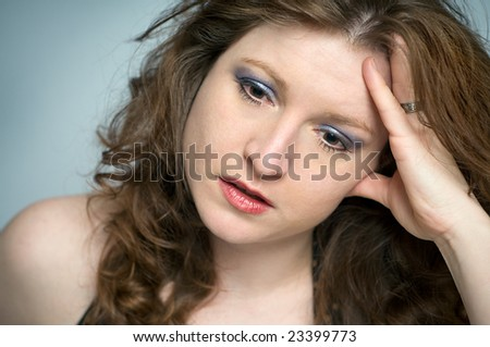 Stressed Woman Portrait looking Upset and Depressed, emotional, disappointed, hurt, or hopeless on blue background