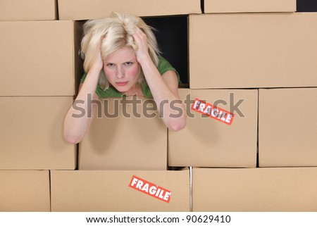 Stressed woman surrounded by boxes - stock photo
