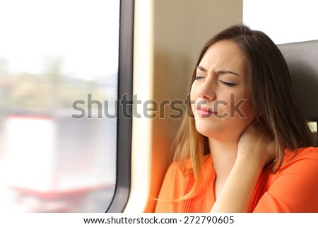 Stressed woman with neck ache sitting in a train wagon complaints - stock photo