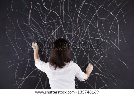 Stressed woman writing in the chalkboard lots of crazy lines - stock photo