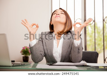 Stressed young business woman doing some breathing exercises and meditating at her office - stock photo