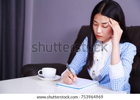 stressed young business woman sitting at her desk and writes a note on the notebook