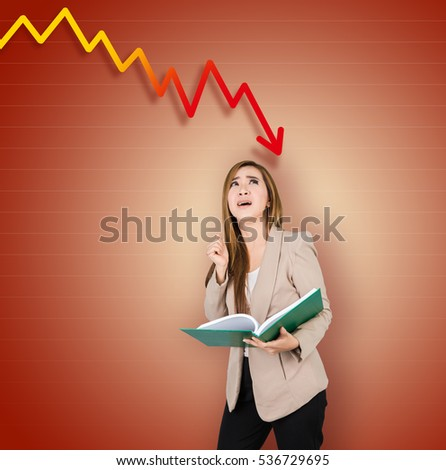 Stressed Young Business Woman Standing Under The Digital Graph with The Arrow Going Down. Concept of Decline and Economical Crisis.