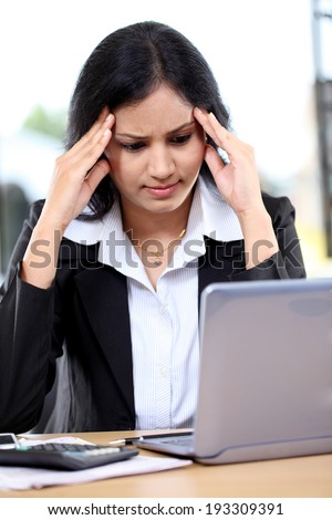Stressed young business woman with tablet computer at office