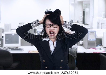 Stressed young businesswoman at workplace - stock photo