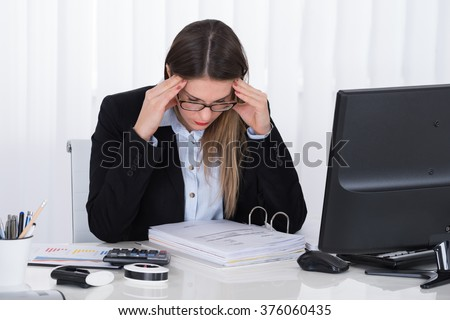 Stressed Young Businesswoman Sitting In Office With Financial Report - stock photo