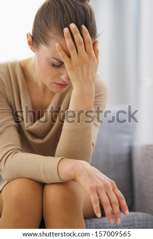 Stressed young housewife sitting on couch - stock photo