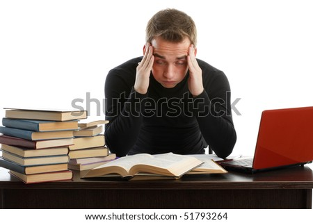 Stressed young man sitting at a table among books and  laptop on a white background