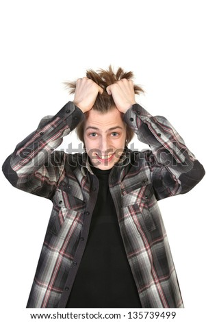 Stressed young man tear his hair out, crazy face expression on the white background
