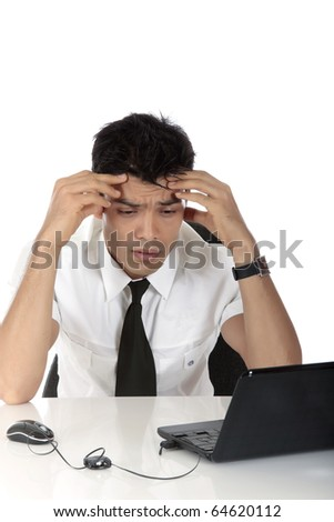 Stressed young Nepalese businessman in office at desk in front of a laptop holding his head, worried. Studio shot. White background - stock photo