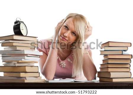 Stressed young woman  at a desk among books on a white background - stock photo