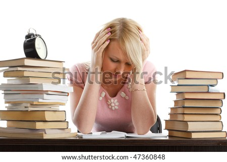 Stressed young woman  at a table among books on a white background - stock photo