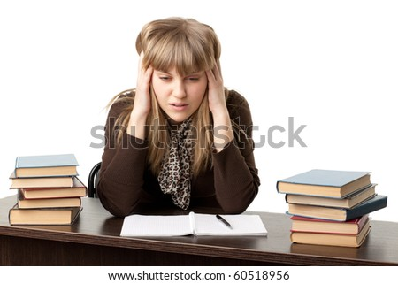 Stressed young woman at a table among books on a white background