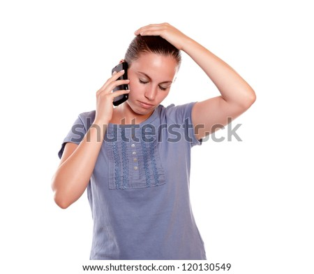 Stressed young woman conversing on cellphone standing over white background