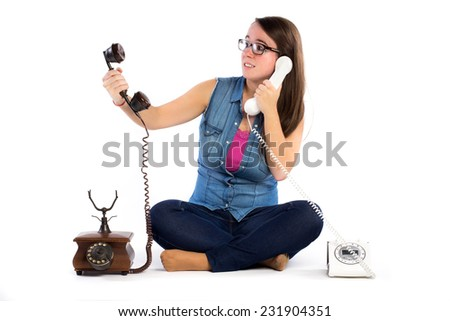 Stressed young woman holding two handset telephones on white background - stock photo
