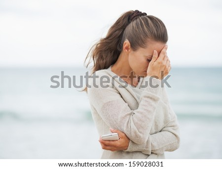 Stressed young woman in sweater on beach with cell phone